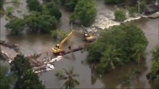 Mechanical diggers building flood defences