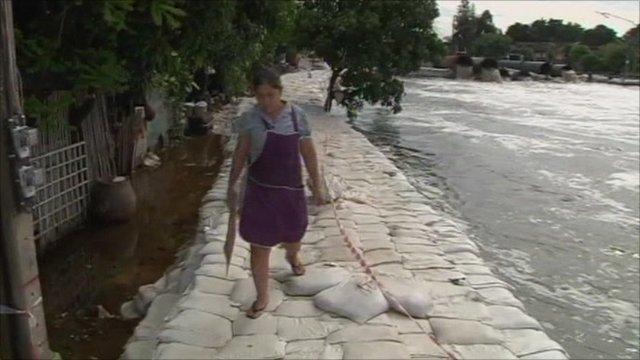 Woman walking along dam made of sandbags next to swollen river