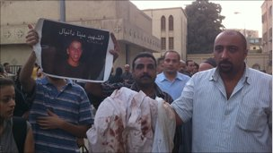 A man shows the bloodstained clothes of Mina Daniel outside St Mark's Cathedral. Photo by Hamada Abu Qammar
