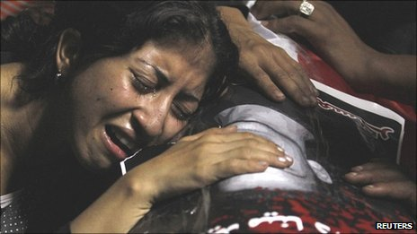 An Egyptian Christian woman mourns on the coffin of Coptic Christian Mina Daniel