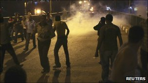 Protesters flee from tear gas during clashes with soldiers in Cairo on 9 October 2011