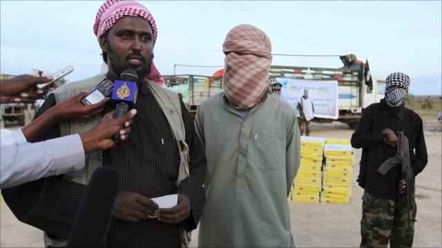"Al Shabaab""s spokesman Sheikh Ali Mohamud Rage (L) and a foreign al-Qaeda official Abu Abdalla al Muhaajir (R) speak to the media as they distribute food rations"