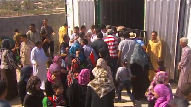 Libyan's gather outside cold storage container holding the body of Gaddafi's son