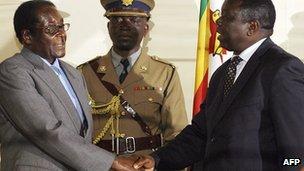 Zimbabwean President Robert Mugabe (L) shakes hands with Movement for Democratic Change leader Morgan Tsvangirai on 21 July 2008