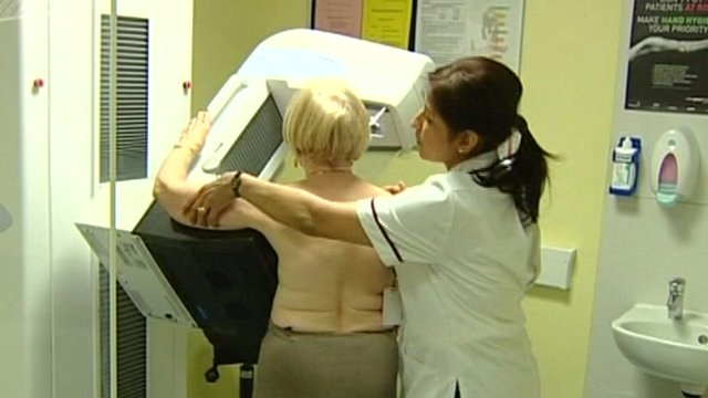 Nurse helping woman through screening