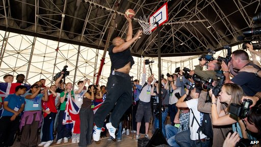 Former NBA basketball star John Amaechi throws a basketball into the hoop