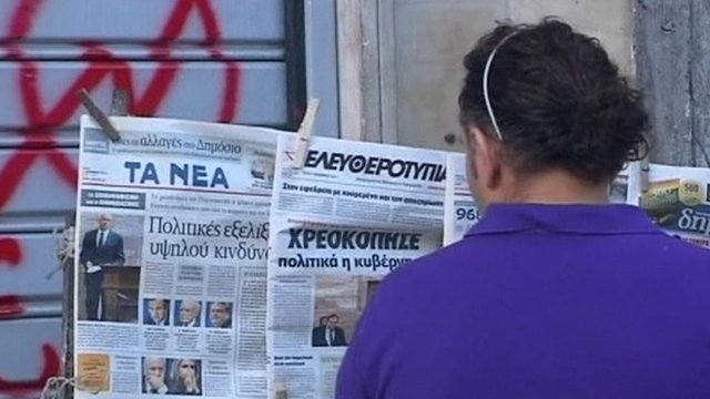 Man in Greece looking at newspapers