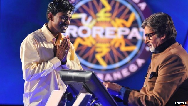 Sushil Kumar joins his hands together past Bollywood actor Amitabh Bachchan after winning about $1 million on an Indian game show in Mumbai