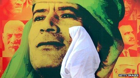 A woman walks past a image of Colonel Gaddafi