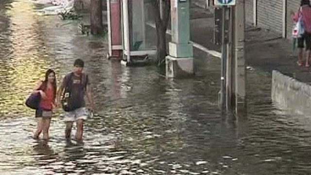 Couple walking through knee-deep waster in Bangkok street