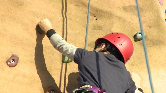 Boy climbing up a climbing wall
