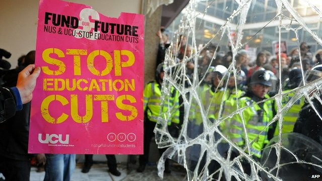Demonstrator holds a placard next to a broken window in 2010