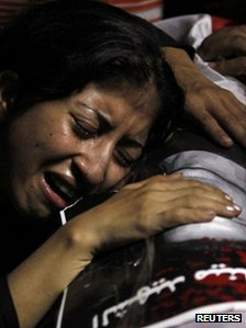 An Egyptian Christian woman mourns on the coffin of a fellow Christian who was killed during clashes with soldiers and riot police in October