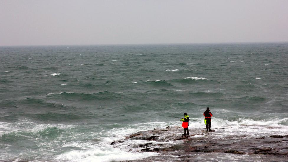 Fishermen standing on rocks