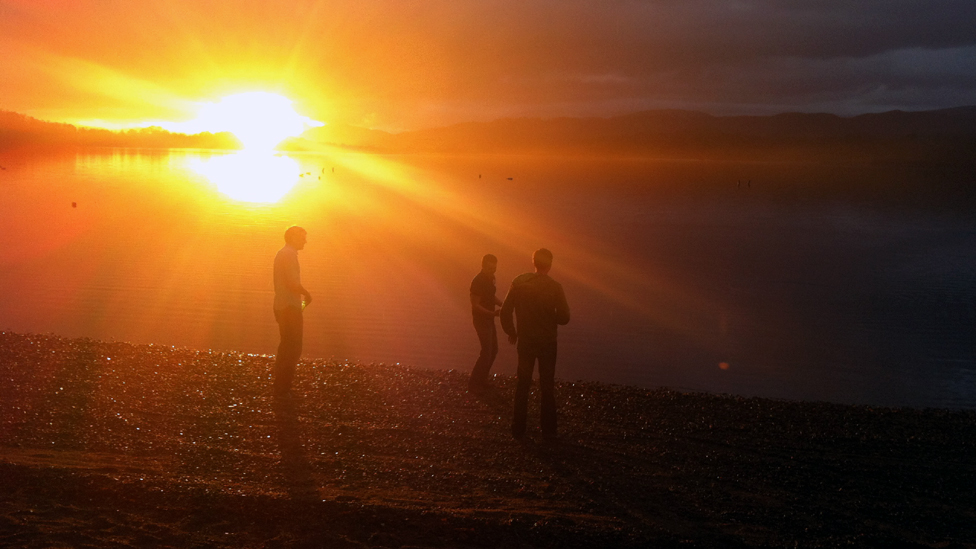 Men standing on the shore of Loch Insch at sunset