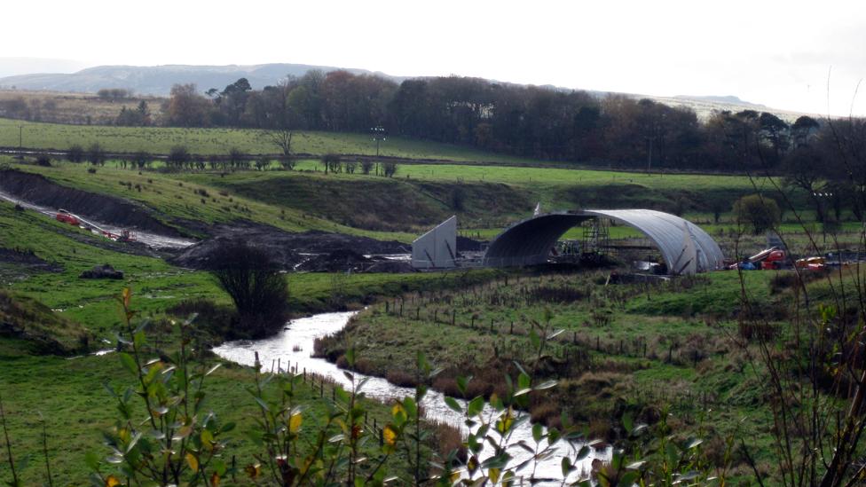 Precast bridge being erected over a river