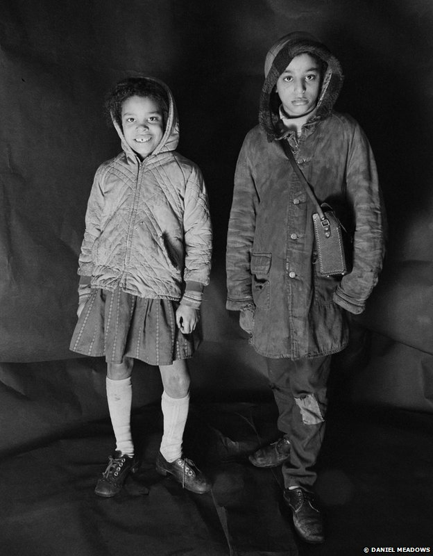 Portrait of Angela Loretta Lindsey, aged 8, with her brother Mark Emanuel Lindsey in Meadows' free photographic shop on Greame Street, Moss Side, Manchester, February - April 1972