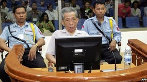 """Kaing Guek Eav better known as """"Duch"""" (C) sits in a dock in the court room at the Extraordinary Chambers in the Courts of Cambodia in Phnom Penh on December 5, 2008"""