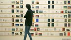 A woman looks at the annual Royal College of Art Secret Postcards exhibition