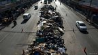 Vehicles drive past a refuse pile in the centre of the main road in Bangkok