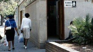 Black woman walk past whites-only toilet