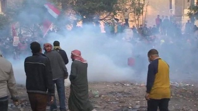 Protesters gathered with Egyptian flags in clouds of tear gas