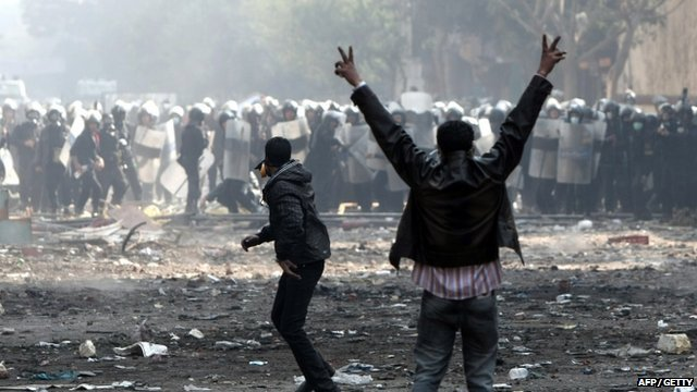 An Egyptian protester shows the V-sign for victory during clashes with riot police