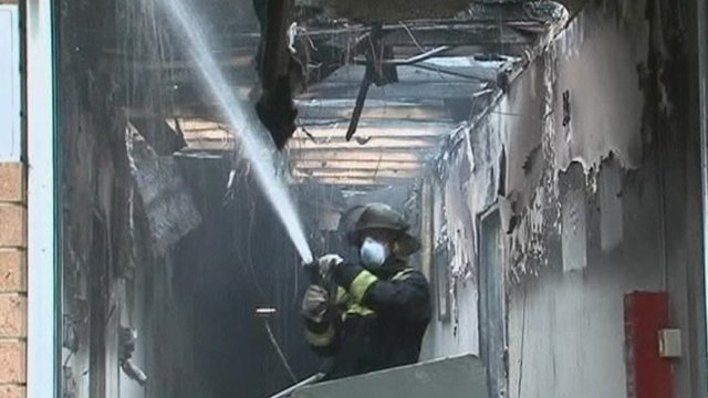 Firefighter hoses down burned building