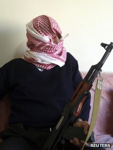 Weapons dealer Abu Wael, covering his face with an Arab keffiyeh headdress and clutching one of his rifles, speaks with Reuters, in Lebanon's Bekaa valley, November 21, 2011.