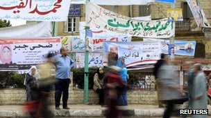 People walk past election campaign banners in Cairo (27 November 2011)