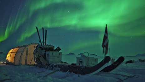 Aurora borealis over a tent of the Sirius Patrol in northern Greenland