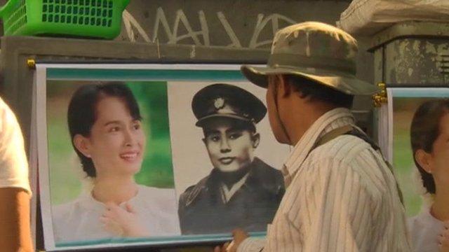 Man looks at photo of Aung San Suu Kyi