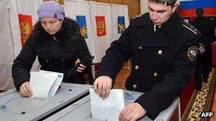 A Russian woman (L) and a sailor vote in Vladivostok, Russia - 4 December 2011