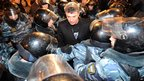 Police surround Russian opposition leader Boris Nemtsov during protests in central Moscow on 6 December 2011