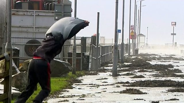 A man struggles to walk in the wind