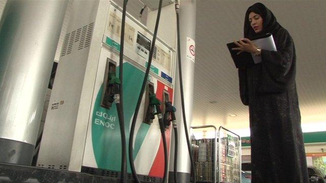 An Emirati woman standing next to a petrol pump