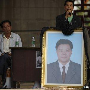 Protesters show a portrait of deceased village leader Xue Jinbo