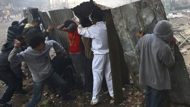 Protesters take cover near Tahrir Square in Cairo on 16 December