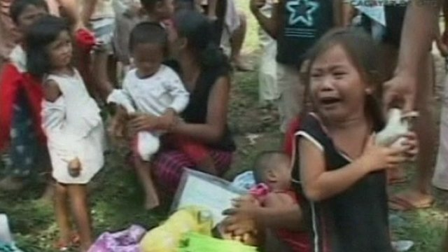 Girl weeps following devastating floods in the Philippines.