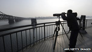 A Chinese man use binoculars for a closer look into North Korea from the end of the Broken Bridge along the Yalu River in the Chinese border city of Dandong