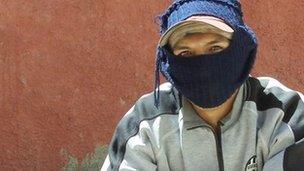 Shoeshiner wearing balaclava in La Paz