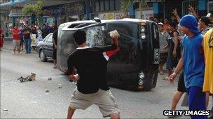 Man throws brick at car