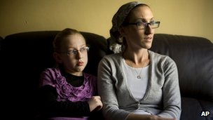 Naama Margolese, 8, sits with her mother Hadassa in their home in the central Israeli town of Beit Shemesh