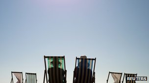 Sunbathers sit on deck chairs at Brighton beach on 29 September