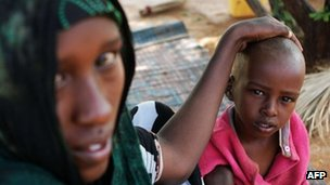 Refugee Abshiro Isakbul sits by her sick son at the Transit Centre in Dolo Ado, Ethiopia, on December 15, 2011.
