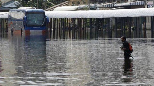 Man wading through flooded station in Bangkok last November