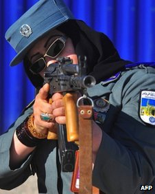 An Afghan female police officer practices aiming with a Kalashnikov assault rifle