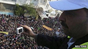 An Arab League observer takes photos for anti-government protesters on the streets in Adlb