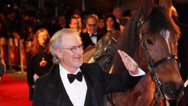 Steven Spielberg pats the horse that plays Joey