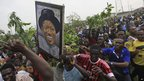 People in Lagos run with a placard of President Goodluck Jonathan as they protest following the removal of fuel subsidy by the government